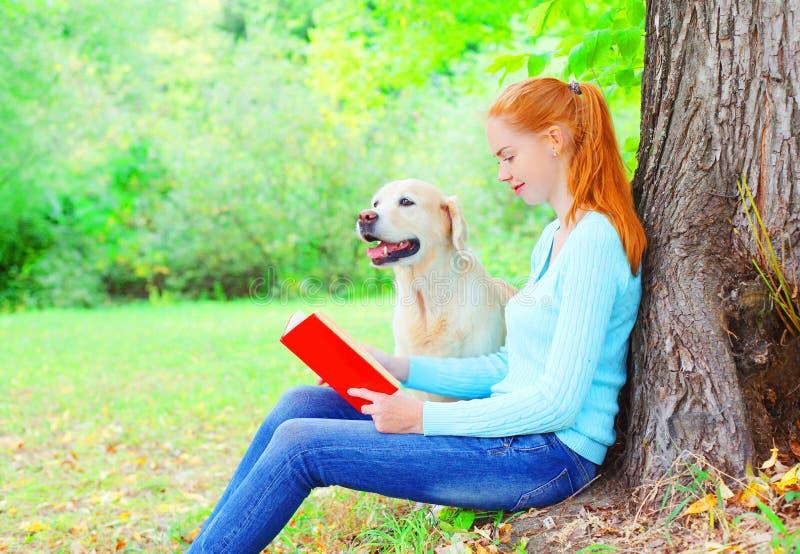 De gelukkige eigenaarvrouw leest een boek met de zitting van de Golden retrieverhond dichtbij boom in het park royalty-vrije stock afbeeldingen