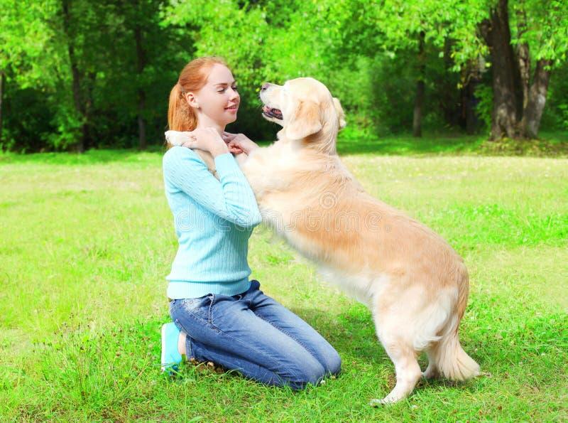 De gelukkige eigenaarvrouw leidt haar Golden retrieverhond op het gras in de zomerpark op stock foto's