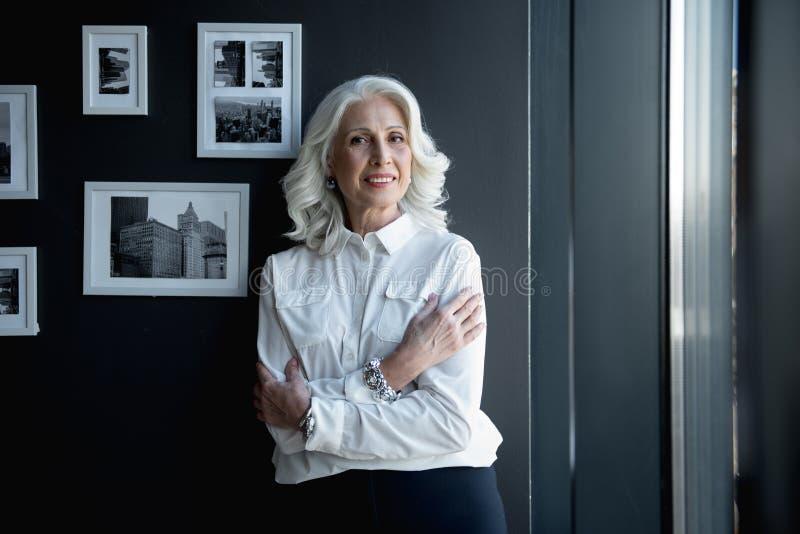 De gelukkige elegante hogere vrouw bevindt zich in bureau stock afbeelding
