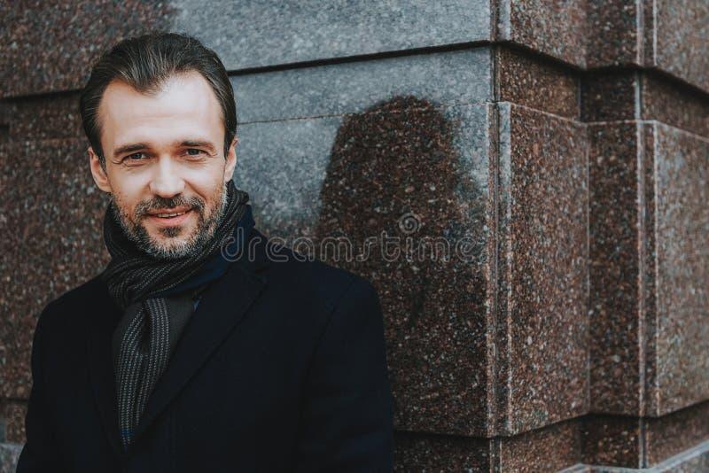 De gelukkige elegante mens in zwarte laag is in openlucht royalty-vrije stock fotografie