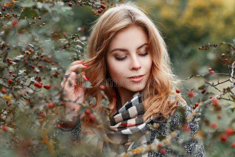 De gelukkige elegante vrij jonge vrouw met uitstekende geruite sjaal in luxueuze warme laag bevindt zich dichtbij een boom in het stock afbeeldingen