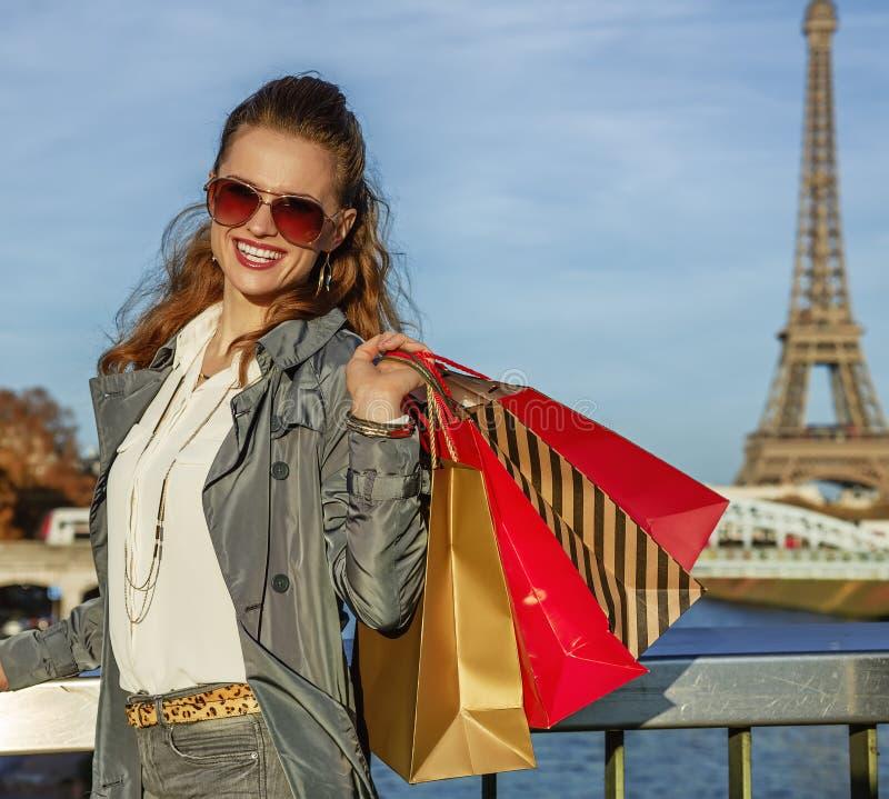De gelukkige elegante vrouw met het winkelen doet dichtbij de toren van Eiffel, Parijs in zakken stock fotografie