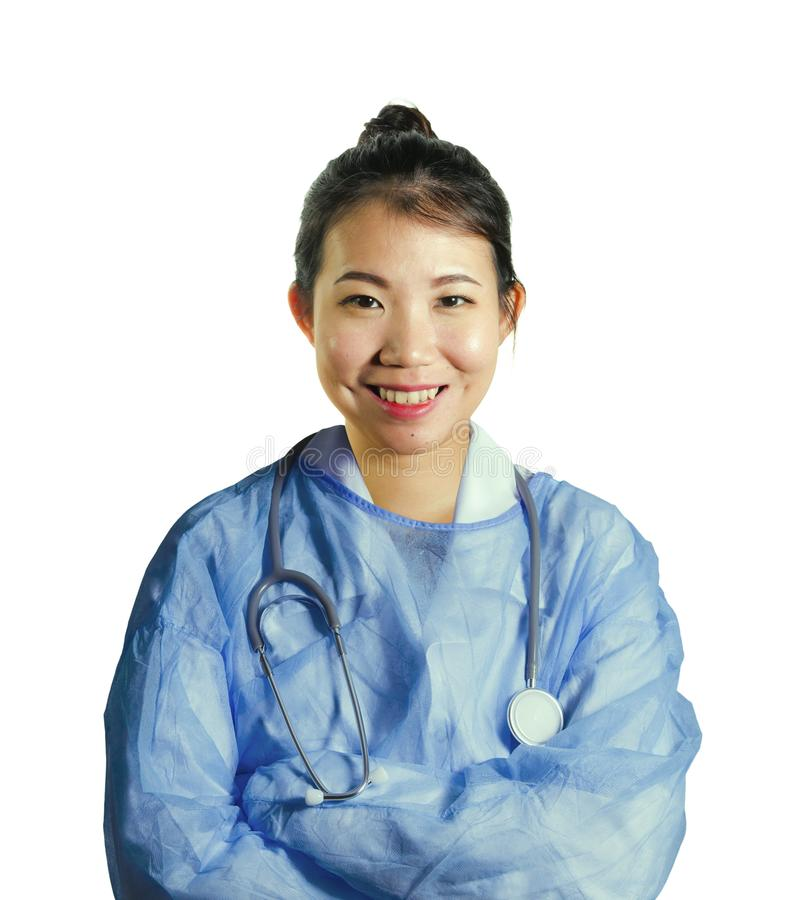 De gelukkige en aantrekkelijke Aziatische Koreaanse geneeskunde artsenvrouw in blauw schrobt het glimlachen het vrolijke stellen  royalty-vrije stock afbeelding