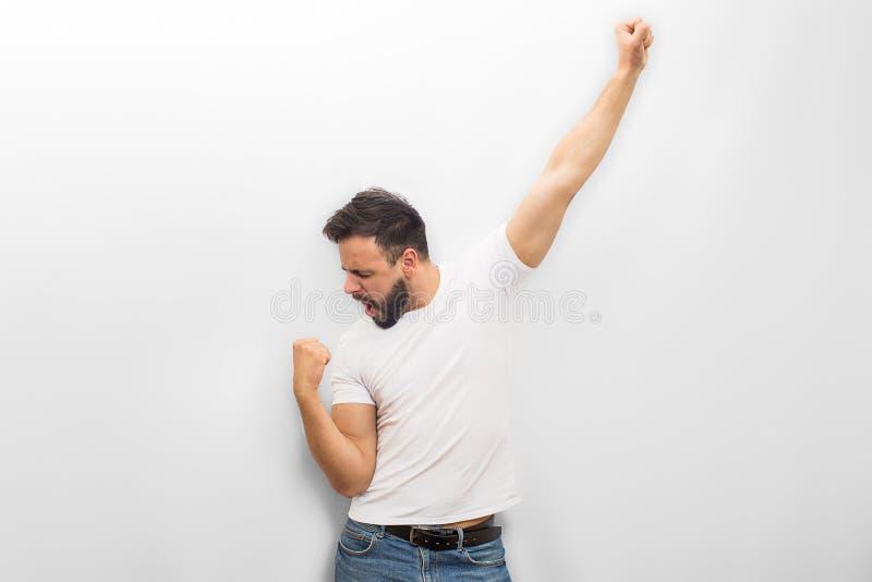 De gelukkige en blije jonge mensentribune en stelt Hij bekijkt zijn vuist en houdt omhoog een andere hand Geïsoleerdj op witte ac royalty-vrije stock foto