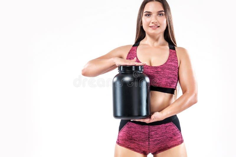 De gelukkige en gezonde spier jonge fitness atleet van de sportenvrouw met een kruik sportenvoeding - proteïne, gainer en stock foto