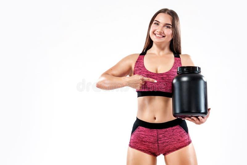 De gelukkige en gezonde spier jonge fitness atleet van de sportenvrouw met een kruik sportenvoeding - proteïne, gainer en royalty-vrije stock afbeelding