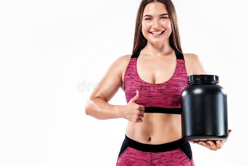De gelukkige en gezonde spier jonge fitness atleet van de sportenvrouw met een kruik sportenvoeding - proteïne, gainer en royalty-vrije stock foto