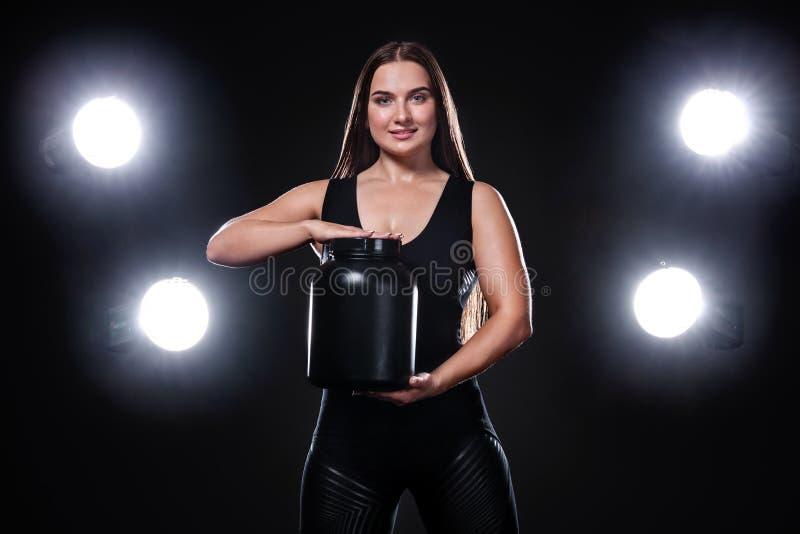 De gelukkige en gezonde spier jonge fitness atleet van de sportenvrouw met een kruik sportenvoeding - proteïne, gainer en stock afbeelding