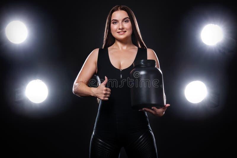 De gelukkige en gezonde spier jonge fitness atleet van de sportenvrouw met een kruik sportenvoeding - proteïne, gainer en caseïne stock afbeelding