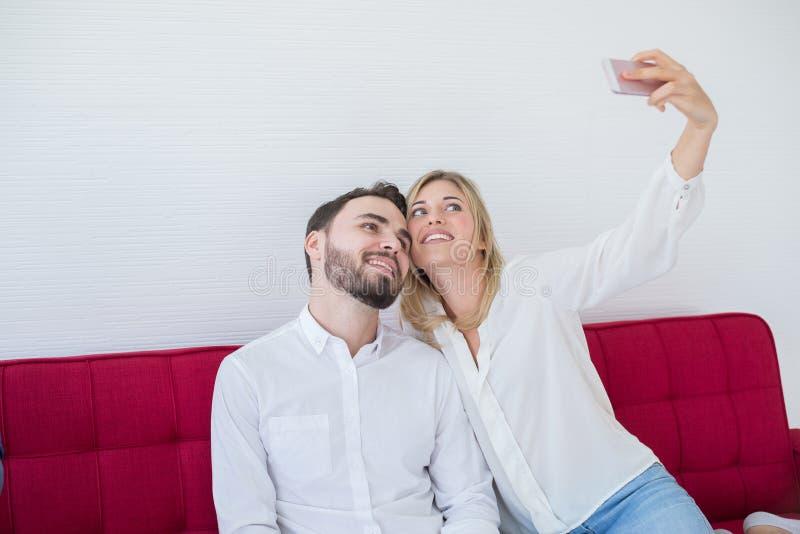 De gelukkige en glimlachende tiener van de paarminnaar maakt samen thuis selfie met celtelefoon royalty-vrije stock foto