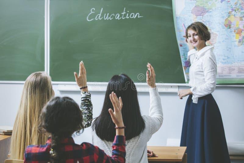 De gelukkige en jonge studenten van de leraarsvrouw die hun handen ophieven is stock afbeelding