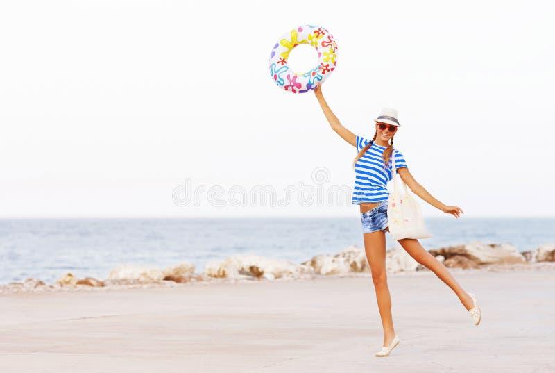 De gelukkige en kleurrijke dragende zonnebril van de strandvrouw en strandhoed die de zomerpret hebben tijdens reisvakantie stock foto