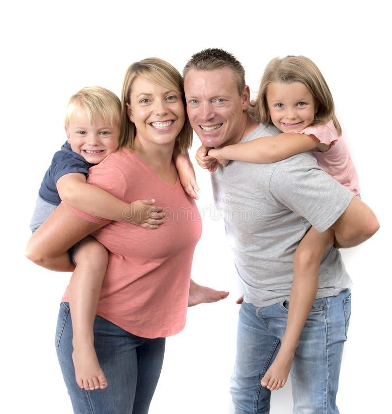 De gelukkige en mooie Amerikaanse familie met echtgenoot en vrouw die hun rug dragen weinig zoon en mooie jonge dochter in liefde stock fotografie