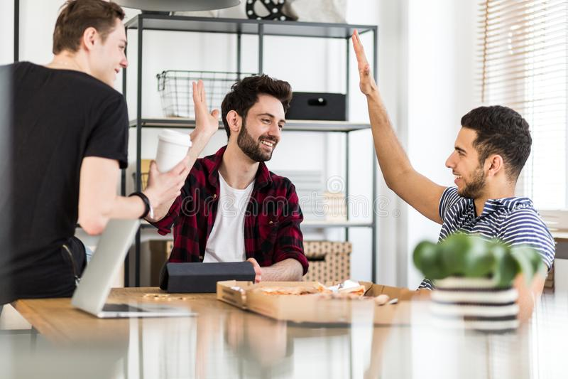De gelukkige en tevreden groep vrienden die pizza eten na handelt af stock foto's