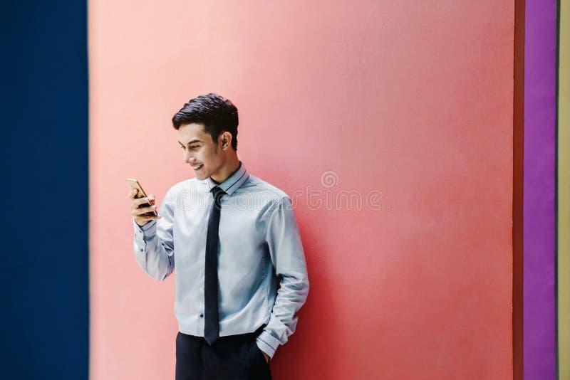 De gelukkige en vriendschappelijke jonge aantrekkelijke Zakenman gebruikt Slim phon stock foto's