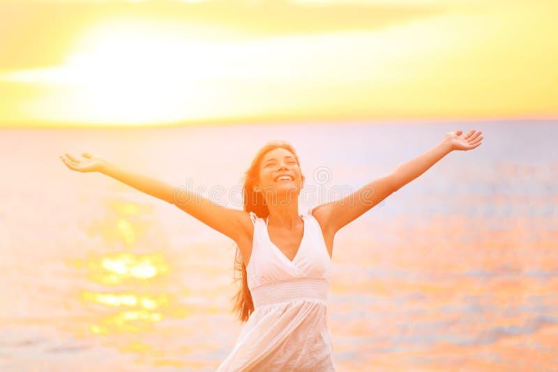 De gelukkige en vrije open wapens van de vrijheidsvrouw op strand stock afbeelding