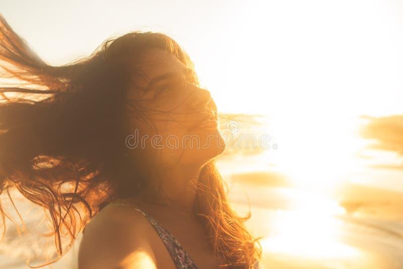 De gelukkige en vrije open wapens van de vrijheidsvrouw op strand bij zonnige zonsondergang stock afbeelding