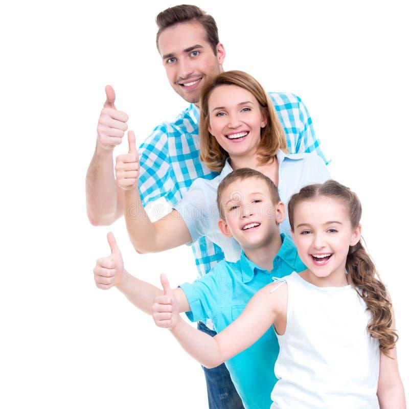 De gelukkige Europese familie met kinderen toont de duimen omhoog ondertekenen stock foto