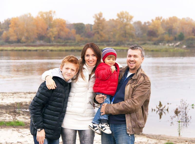 De gelukkige familie bevindt zich dichtbij de rivier in de de herfstdag stock afbeeldingen