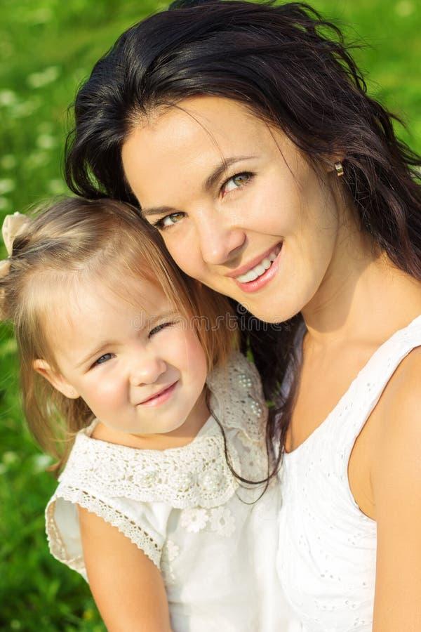 De gelukkige familie, de moeder en de dochter kleedden zich in witte zitting op het gras in een Park op een Zonnige de zomerdag stock foto's