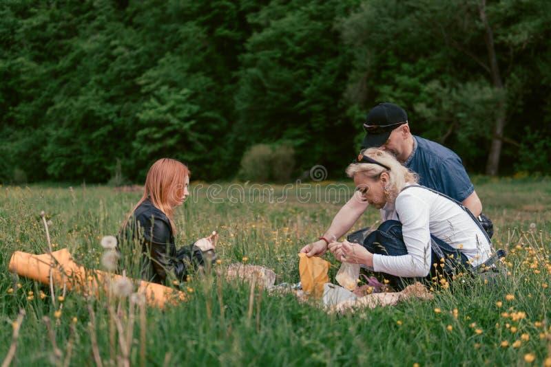 De gelukkige familie die lunch hebben en drinkt thee het kamperen, weekend, picknick man, vrouw, meisje stock afbeelding