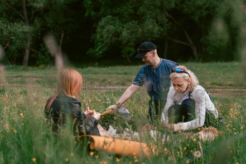De gelukkige familie die lunch hebben en drinkt thee het kamperen, weekend, picknick man, vrouw, meisje royalty-vrije stock fotografie