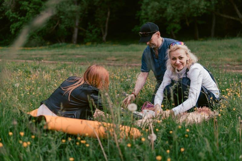 De gelukkige familie die lunch hebben en drinkt thee het kamperen, weekend, picknick man, vrouw, meisje royalty-vrije stock foto