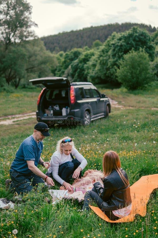 De gelukkige familie die lunch hebben en drinkt thee het kamperen, weekend, picknick man, vrouw, meisje, Oversteekplaats, SUV-aut stock fotografie