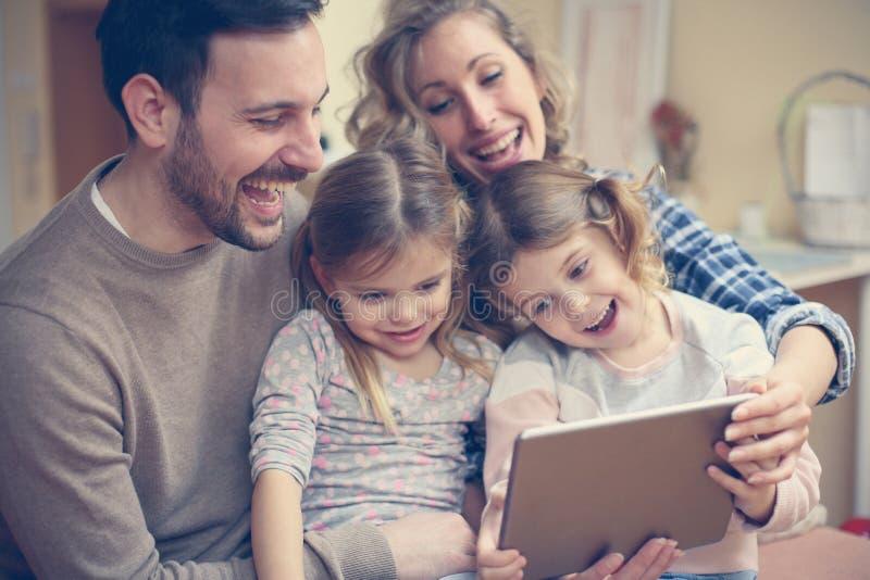 De gelukkige familie geniet thuis van stock foto