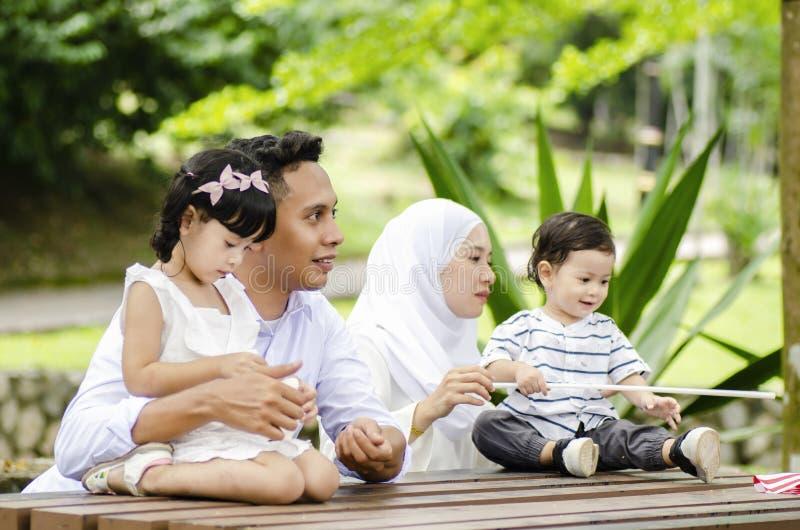 De gelukkige familie geniet van hun weekend bij openbaar park tijdens de zomer royalty-vrije stock foto's