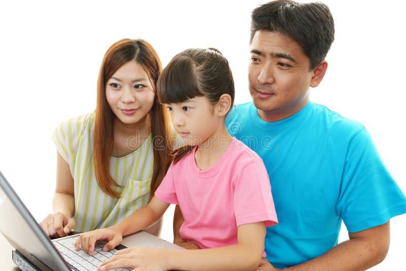 De gelukkige familie geniet van laptop stock foto's