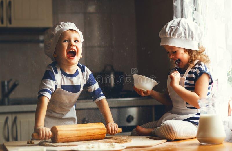 De gelukkige familie grappige jonge geitjes bakken koekjes in keuken stock fotografie