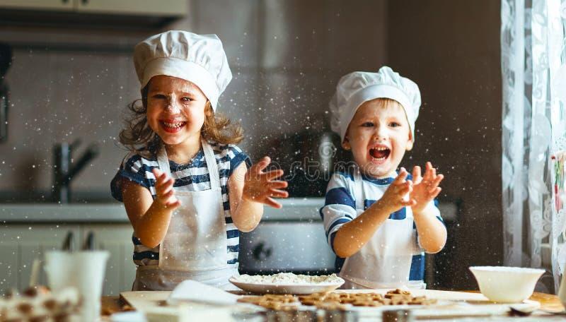 De gelukkige familie grappige jonge geitjes bakken koekjes in keuken stock foto's