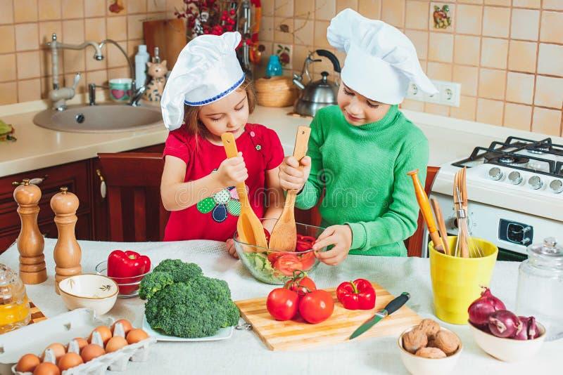 De gelukkige familie grappige jonge geitjes bereiden verse groentesalade in de keuken voor stock fotografie