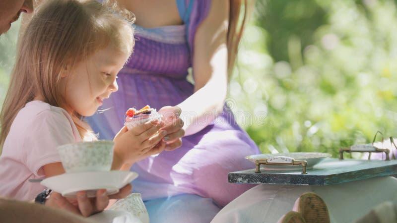 De gelukkige familie heeft in openlucht ontbijt in groen park - moeder, vader en dochter royalty-vrije stock foto