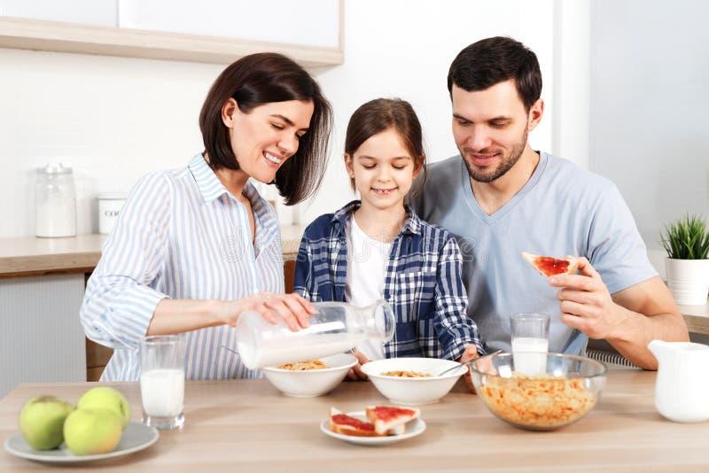 De gelukkige familie heeft samen gezond ontbijt De glimlachende moeder giet melk in kom met cornflakes, eet appelen, snacks en stock afbeeldingen