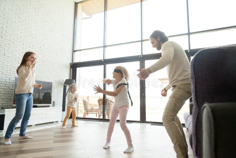 De gelukkige familie het spelen huid - en - zoekt spel in luxehuis royalty-vrije stock afbeelding