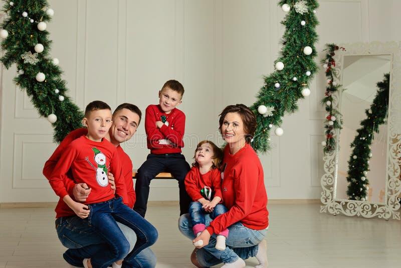 De gelukkige familie in identieke sweaters zit op een schommeling in de winter in het midden van Kerstmisvakantie stock afbeeldingen