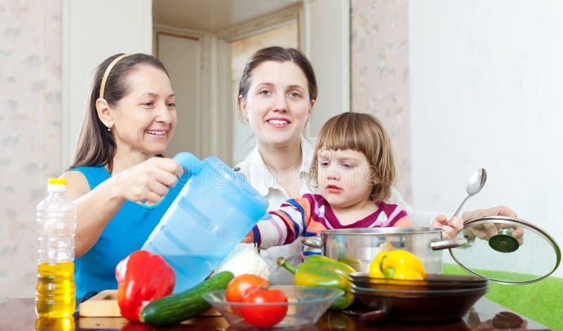De gelukkige familie kookt samen met groenten stock afbeeldingen