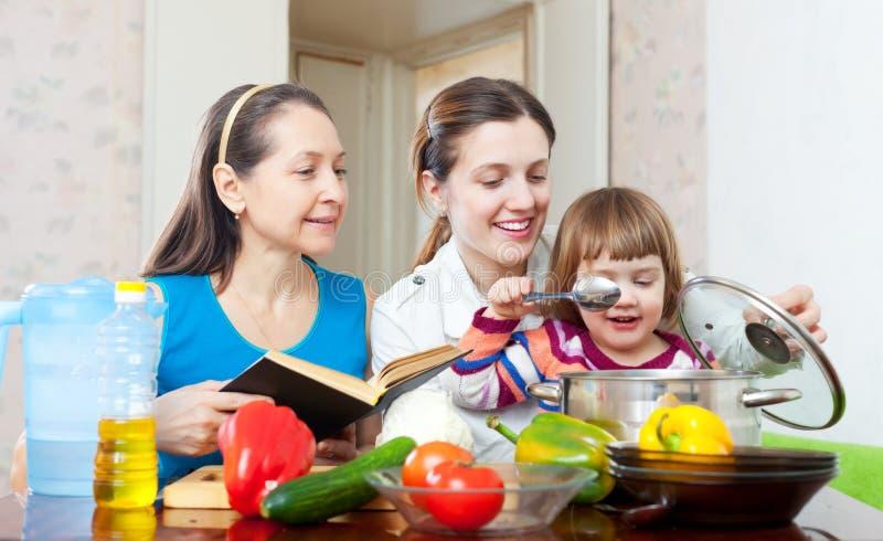 De gelukkige familie kookt samen met kookboek stock foto's