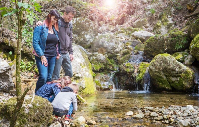 De gelukkige familie let op de bergstroom royalty-vrije stock fotografie