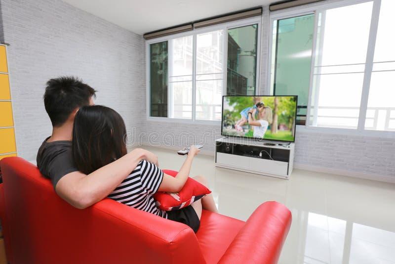 De gelukkige familie let op televisie terwijl het zitten op de bank royalty-vrije stock afbeeldingen