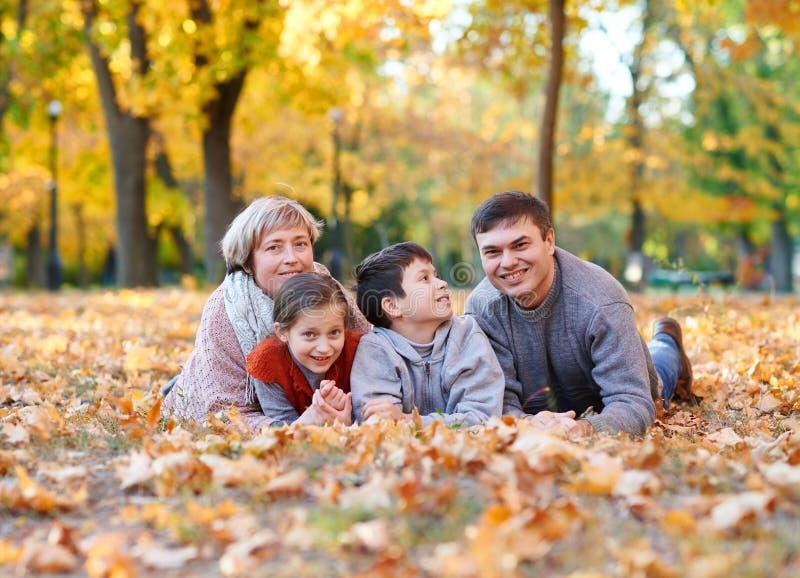 De gelukkige familie ligt in het park van de de herfststad op gevallen bladeren Kinderen en ouders die, en pret stellen glimlache stock foto