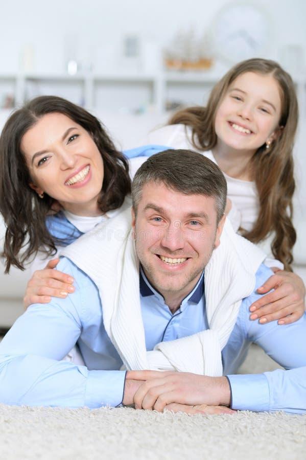 De gelukkige familie met dochter ligt omhelzend royalty-vrije stock afbeeldingen