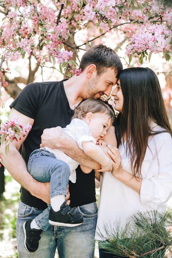 De gelukkige familie met een kind in hun dient zwart-witte kleren in bevindt zich door de boom van kersenbloesems stock afbeelding
