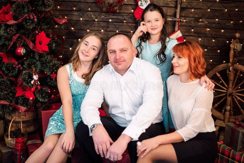 De gelukkige familie met Kerstmis stelt dichtbij de Kerstboom voor Retoucheerd schot stock afbeeldingen