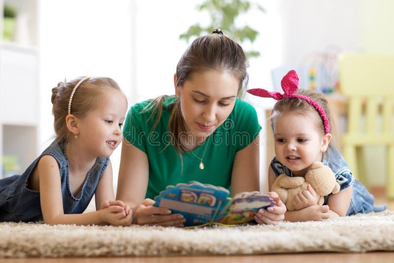 De gelukkige familie met kinderen las een verhaal leggend op de vloer in de jonge geitjesruimte stock foto