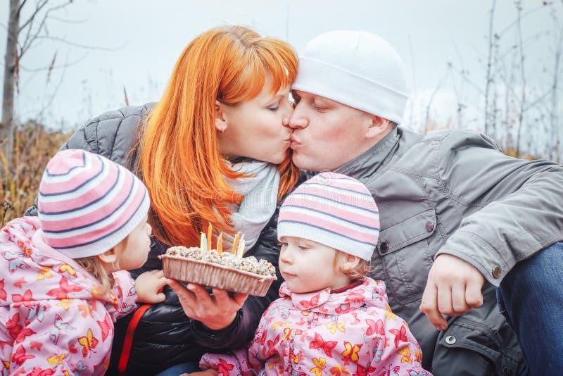 De gelukkige familie met twee 1 éénjarigemeisjes heeft rust op een geel gebied royalty-vrije stock fotografie