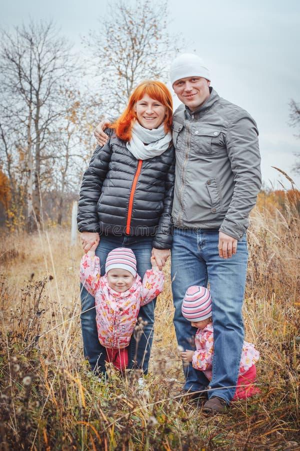 De gelukkige familie met twee 1 éénjarigemeisjes heeft rust op een geel gebied royalty-vrije stock foto