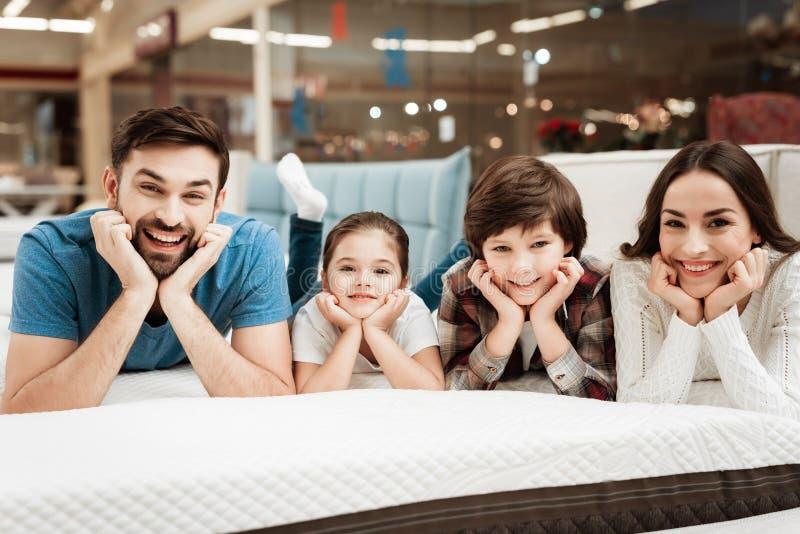 De gelukkige familie ontspant op matras in orthopedische meubilairopslag De grote familie controleert samen zachtheid van matras royalty-vrije stock foto
